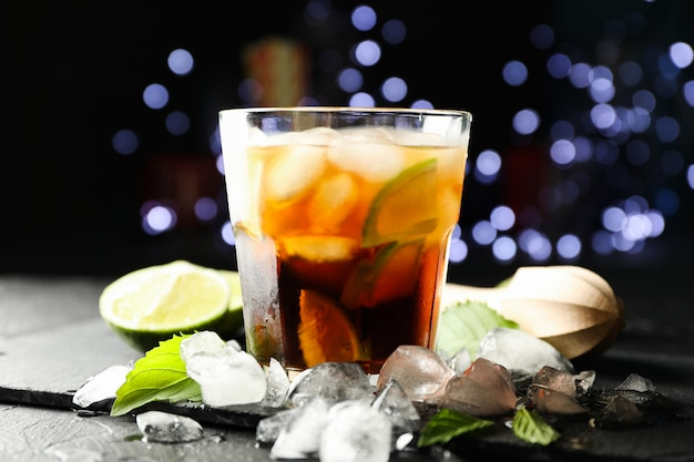 Vetro con fette di cola e lime, spremiagrumi, ghiaccio, menta su sfondo di luci sfocate