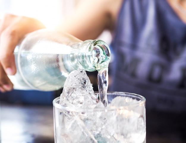 Vetro con ghiaccio e le mani stanno versando acqua potabile rinfrescante e dissetarsi in estate