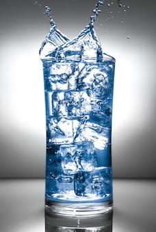 Vetro con ghiaccio e spruzzi di liquidi