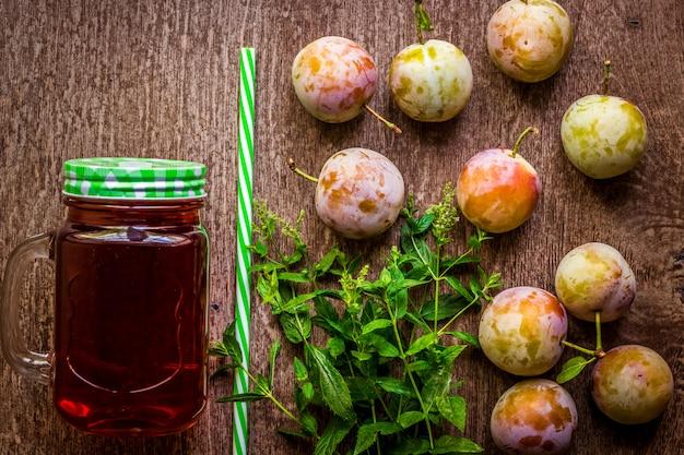 Vetro con plum juice fresco e la menta verde sulla tavola di legno d'annata