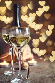 Vetro con vino il romantico giorno di san valentino con luci sfocate