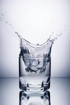 Vetro con vodka, alcool, acqua su uno sfondo grigio con pezzi di ghiaccio che cadono ad esso con spruzzi