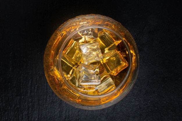 Vetro con whisky e ghiaccio sulla tavola nera. vista dall'alto.
