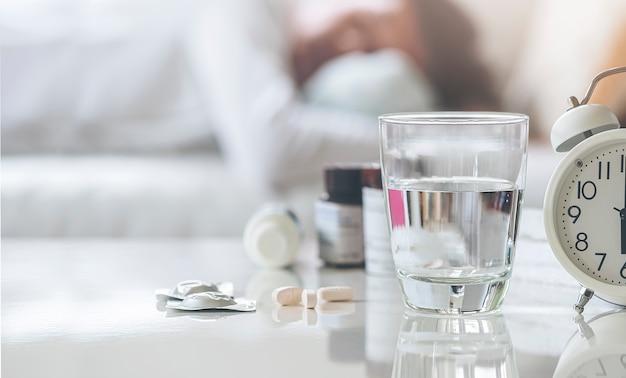 Vetro del primo piano dell'acqua della bevanda e delle pillole sulla tavola bianca con fondo vago dell'uomo che dorme sul sofà in salone.