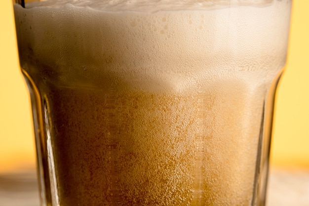 Vetro del primo piano di birra piena di bolle fresca