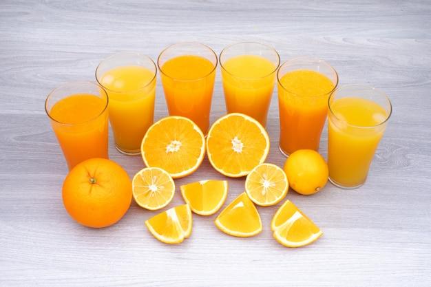 Vetro del succo di limone e dell'arancia sulla tabella bianca