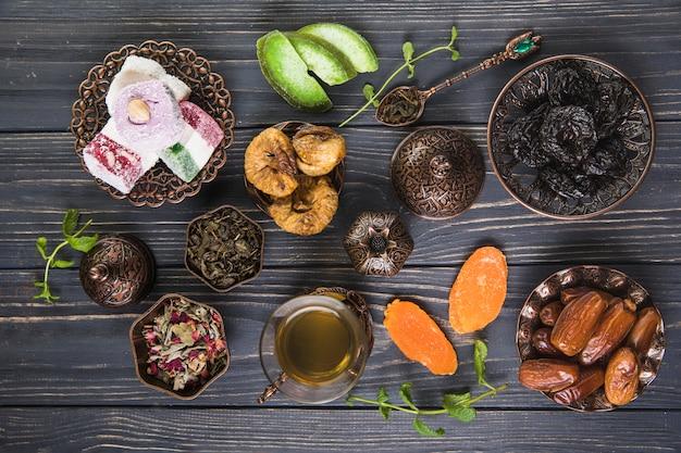 Vetro del tè con diversi tipi di frutta secca sulla tavola di legno