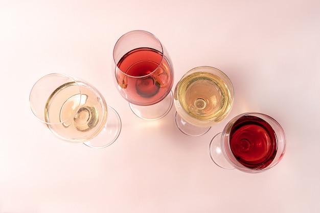 Vetro del vino rosso e vetro di vino rosato e vetro di vino bianco sul rosa.