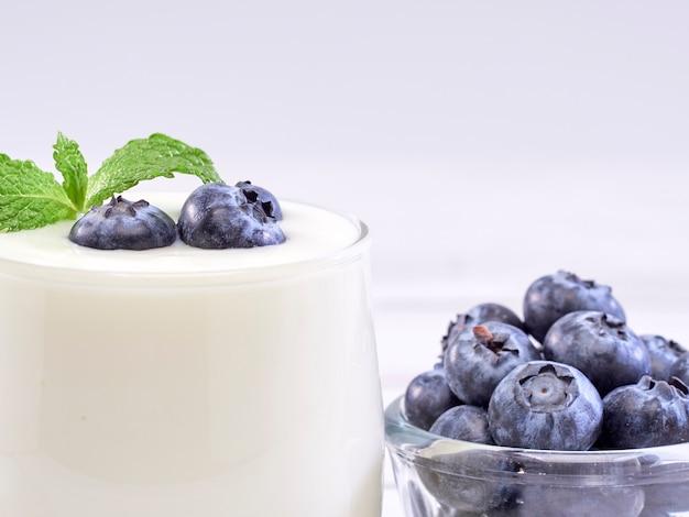 Vetro del yogurt di mirtillo sulla tavola di legno bianca