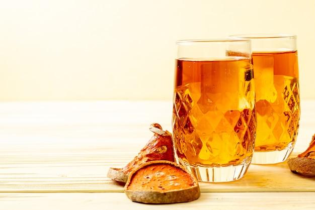 Vetro della bevanda di erbe della frutta di bael su legno