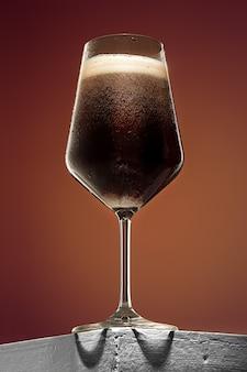 Vetro di birra scura schiumosa fredda su una vecchia tavola di legno