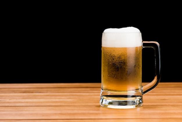 Vetro di birra sulla tavola di legno isolata sulla parete nera, progettazione di massima bevente dell'oggetto di celebrazione dell'alcool