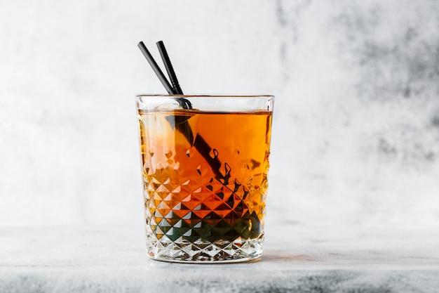 Vetro di tè nero ghiacciato con il limone isolato su fondo di marmo luminoso. vista dall'alto, copia spazio. pubblicità per menu bar. menu della caffetteria. foto orizzontale.