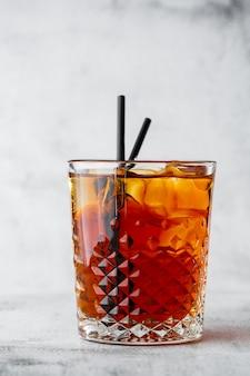 Vetro di tè nero ghiacciato con il limone isolato su fondo di marmo luminoso. vista dall'alto, copia spazio. pubblicità per menu bar. menu della caffetteria. foto verticale.