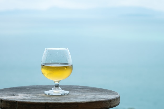Vetro di vino bianco del primo piano sulla tavola sul fondo di vista del mare