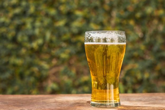 Vetro di vista frontale con birra sulla tavola
