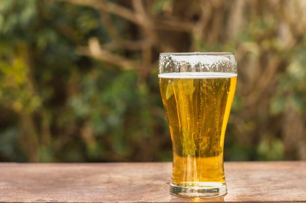 Vetro di vista laterale con birra sulla tavola