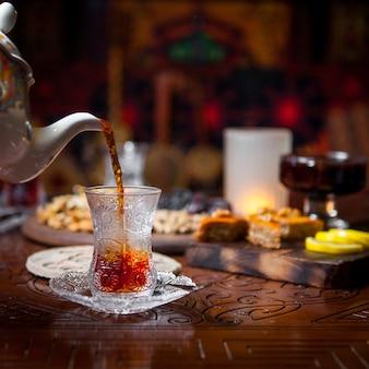 Vetro di vista laterale di tè con baklava e limone ed inceppamento in tavola