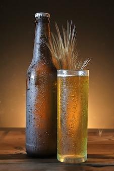 Vetro e bottiglia di birra fredda sul tavolo di legno
