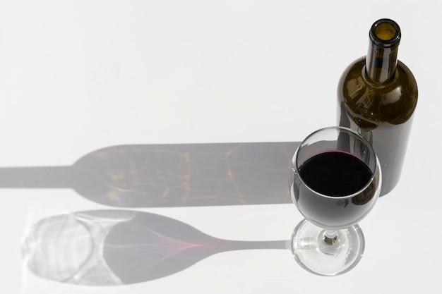 Vetro e bottiglia di vino con le ombre scure isolate su bianco