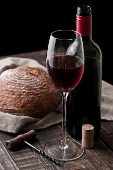 Vetro e bottiglia di vino rosso con la pagnotta fresca con la retro cavaturaccioli in cucina sulla tavola di legno
