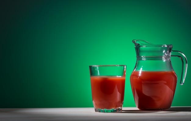 Vetro e brocca di succo di pomodoro su verde