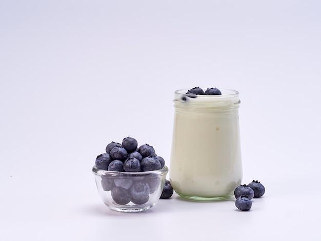 Vetro fresco del yogurt di mirtillo su bianco