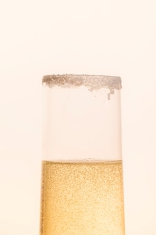 Vetro frontale riempito per metà con champagne scintillante