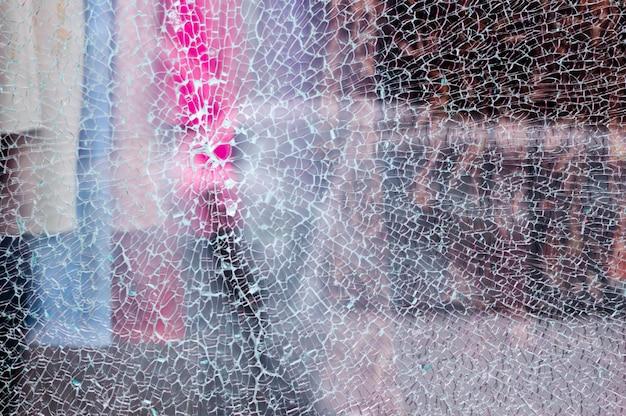 Vetro rotto di una vetrina di un negozio di abbigliamento con sfondo sfocato