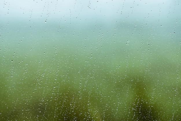 Vetro sporco con gocce di pioggia. gocce di pioggia su sfondo chiaro verde e blu