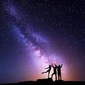 Via lattea. cielo notturno con silhouette di una famiglia felice