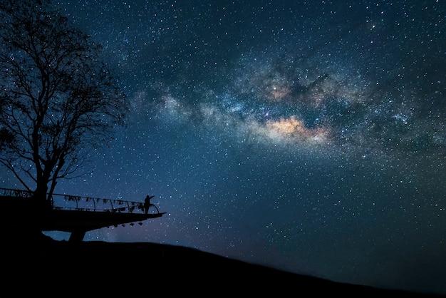 Via lattea di notte. cielo notturno con le stelle e la sagoma dell'uomo alzò le braccia nel cielo