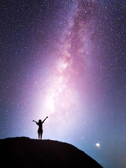Via lattea, stella, con ragazza felice in piedi sulla montagna