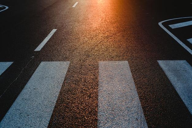 Via solitaria con passaggio pedonale al tramonto, trama con spazio per il testo.
