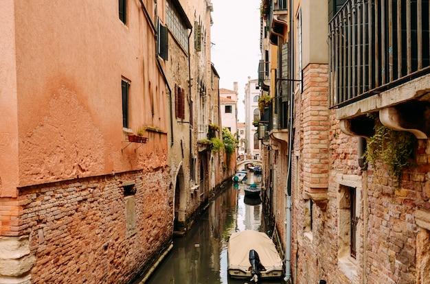 Via tradizionale del canale con la gondola a venezia, italia. canale stretto fra le vecchie case con mattoni a vista variopinte a venezia, italia
