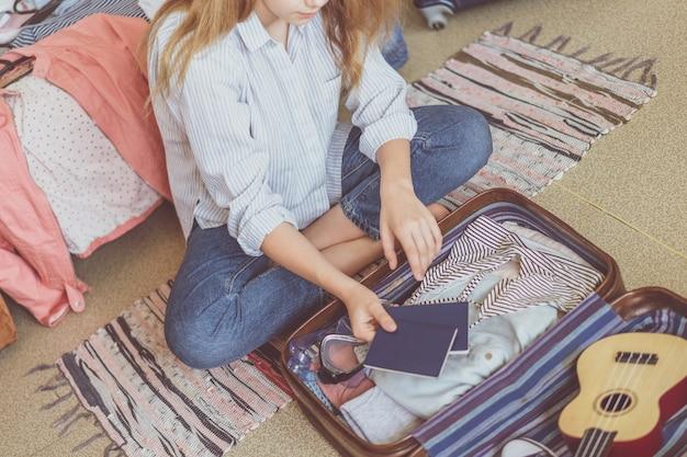 Viaggi estivi e vacanze. valigia dell'imballaggio della giovane donna a casa