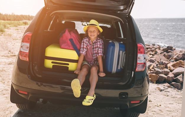 Viaggi, turismo - ragazza con le borse pronte per il viaggio per le vacanze estive. bambino che va all'avventura. concetto di viaggio in auto