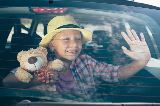 Viaggi, turismo - ragazza con orsacchiotto pronto per il viaggio per le vacanze estive. bambino che va all'avventura. concetto di viaggio in auto