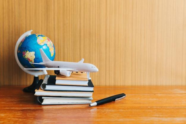 Viaggi, vacanze di viaggio, fine su dell'aeroplano del giocattolo, penna e blocco note e globo sulla tavola di legno
