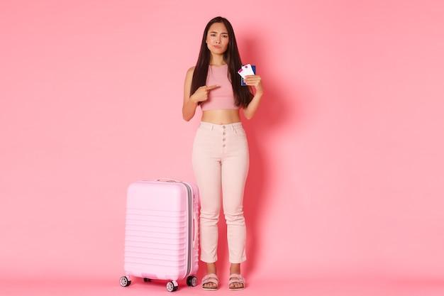 Viaggi, vacanze e concetto di vacanza. a figura intera di turista femminile asiatica delusa e scettica in abiti estivi che si lamenta di una cattiva compagnia aerea, indicando i biglietti aerei e il passaporto