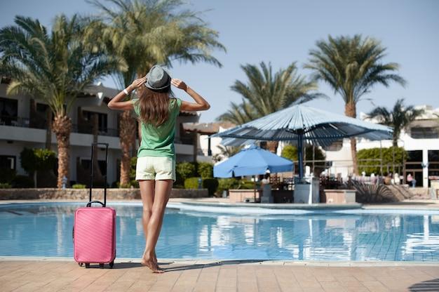 Viaggi, vacanze estive e concetto di vacanza. bella donna che cammina vicino allo stagno dell'hotel