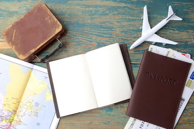 Viaggi, vacanze, turismo - taccuino da vicino, valigia, aeroplano giocattolo e mappa turistica sulla tavola di legno.