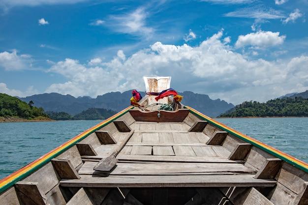 Viaggia in barca longtail alla diga di ratchaprapha a khao sok national park, provincia di surat thani, thailandia.