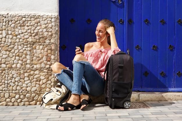 Viaggia la donna che si siede sul marciapiede con la valigia ed il telefono cellulare