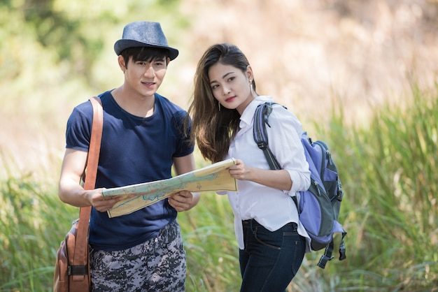 Viaggiando all'aperto con mappa, coppia asiatica.