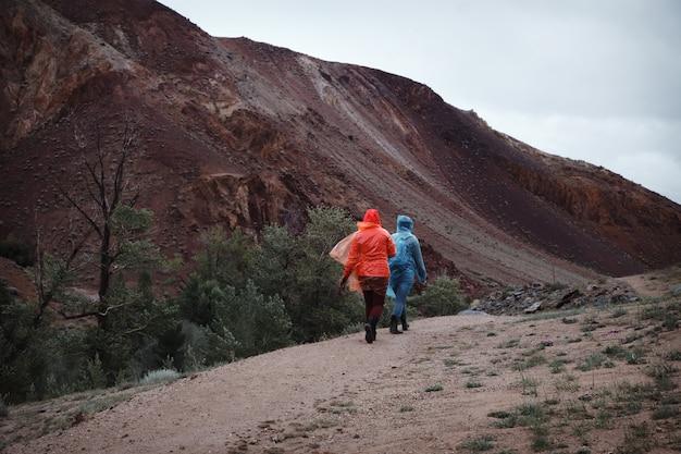 Viaggiano due ragazze di ottimo umore negli impermeabili. il tempo piovoso in montagna impedisce il trekking. vai su un sentiero di montagna.