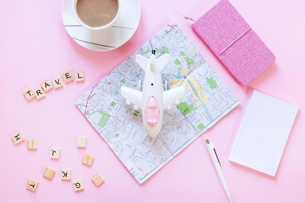 Viaggiare blocchi di legno; carta geografica; carta; tazza di tè; penna; diario e aereo sulla superficie bianca