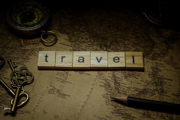 Viaggiare in legno alfabeto sulla mappa antica. - sfondo pubblicitario