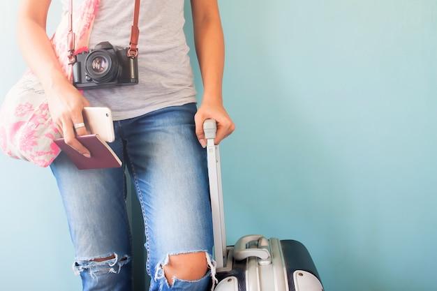 Viaggiare turistico in piedi con la valigia in possesso di passaporto e smart phone