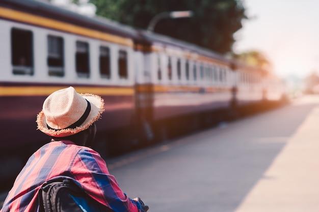 Viaggiatore africano dell'uomo che si siede e che esamina la stazione ferroviaria